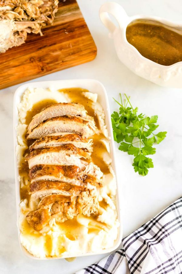 Turkey on a serving platter with gravy.