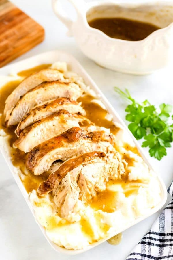 A table set with sliced turkey breasts, gravy, and mashed potatoes.
