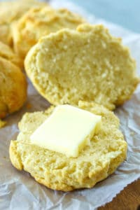 A biscuit split open with a pad of butter on it.