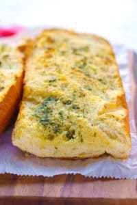 Baked garlic bread on a wooden cutting board.