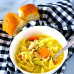 Homemade chicken noodle soup in a white bowl served with rolls.