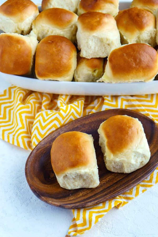 Dinner rolls in a serving bowl and on a wood plate.