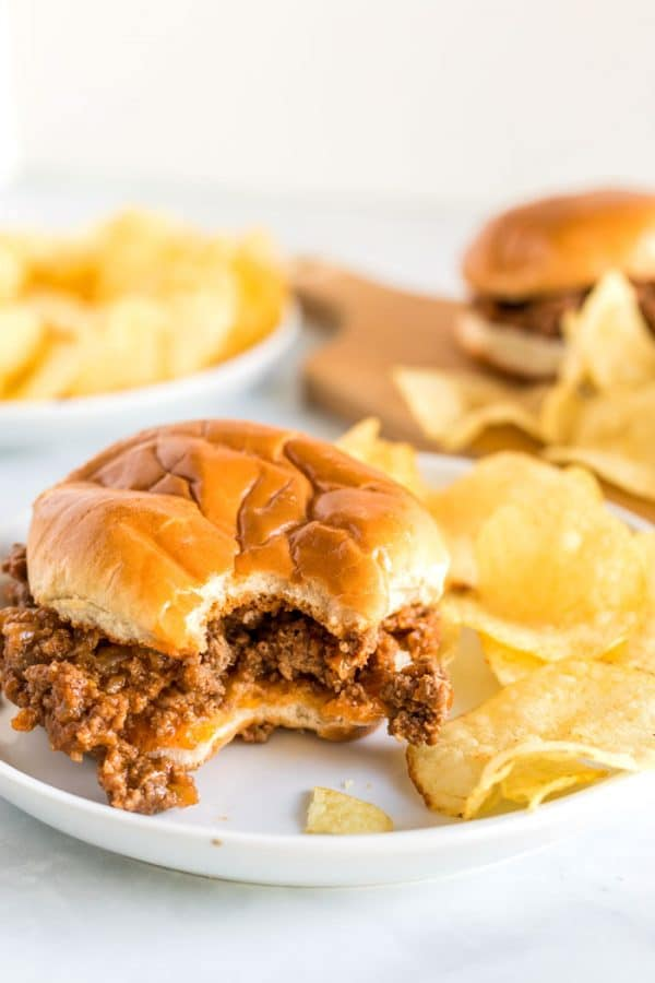 A sloppy joe on a plate with a bite taken out of it.