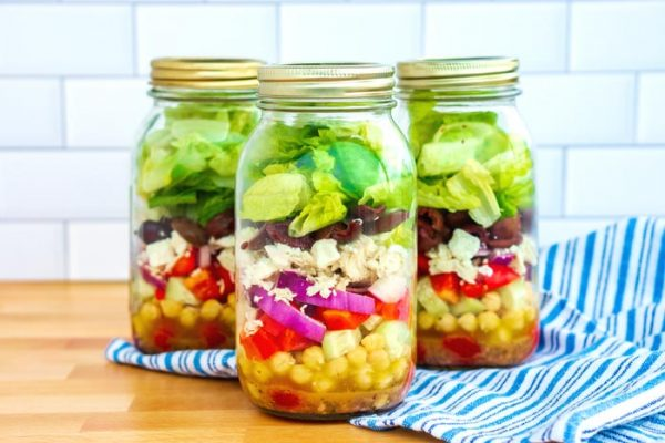 4 cups of Greek salad in a Mason jar.