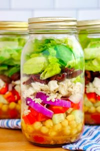 Close up picture of Greek salad in a mason jar.