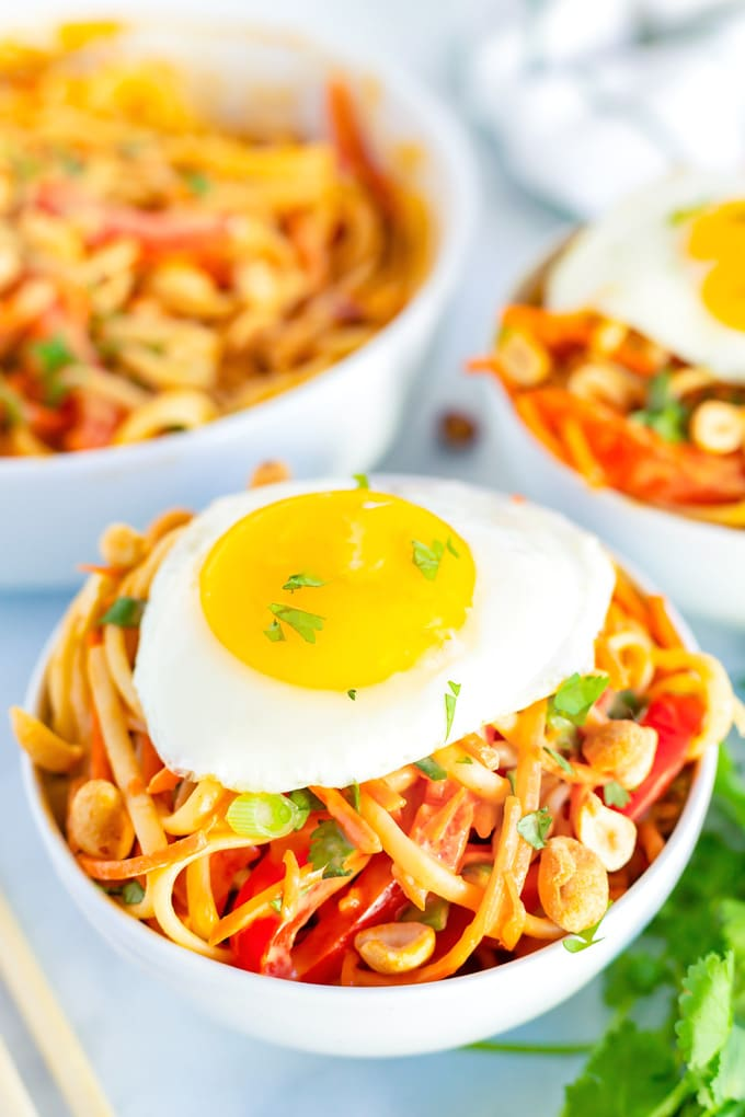 A bowl of Thai peanut noodles with a fried egg on top.