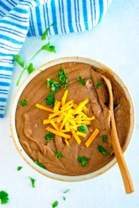 Instant Pot Refried Beans in a serving bowl garnished with cheese and cilantro.