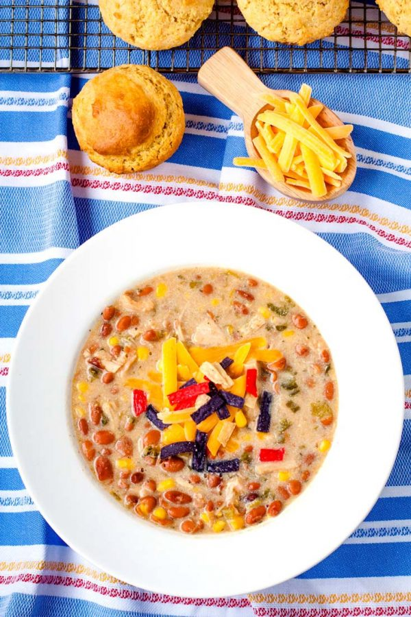 Overhead picture of white chicken chili in a white bowl with shredded cheese and corn muffins.