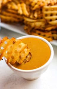 A waffle fry being dipped into Copycat Chick Fil A Sauce.