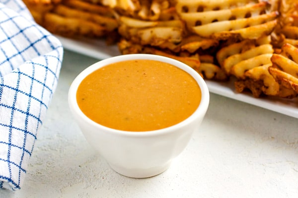 Copycat Chick Fil A Sauce in a white bowl with waffle fries in the background.