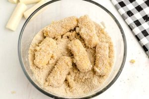 Add the cheese sticks to the bread crumbs to coat.
