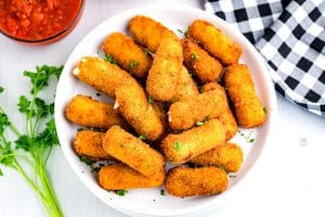 Fried Mozzarella Cheese Sticks on a white plate with dipping sauce in the background.