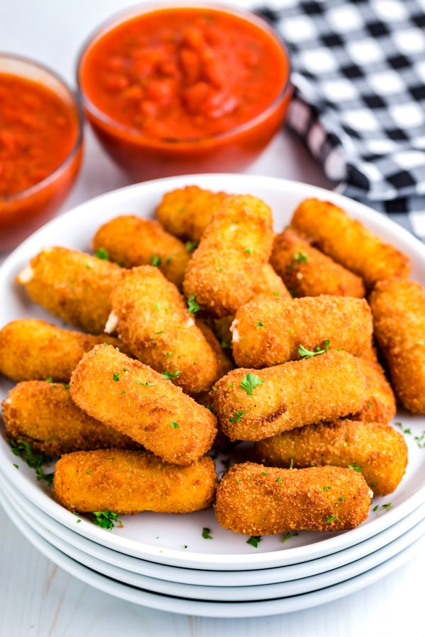 A close up picture of Mozzarella Cheese Sticks on a white plate.
