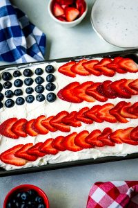 A 4th of July Poke Cake with blueberries and strawberries on it to make it look like an American flag.