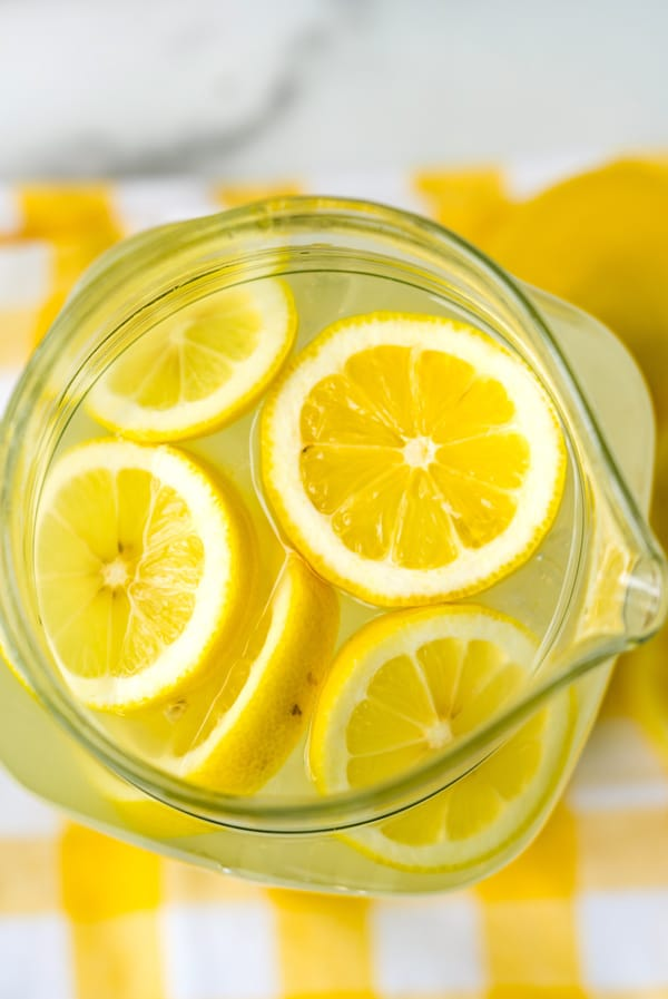 A close up overhead picture of the finished homemade lemonade in a glass pitcher.