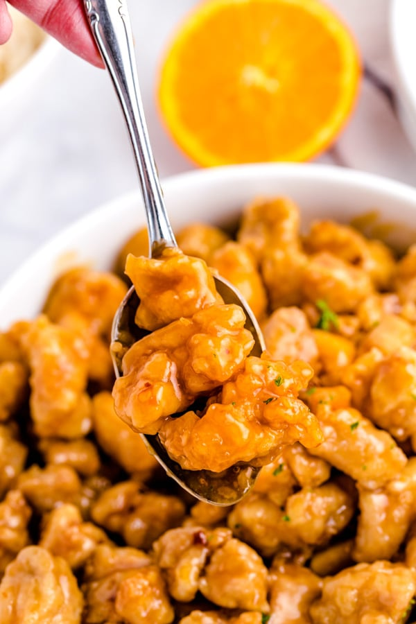 A spoon lifting up pieces of Panda Express Orange Chicken.