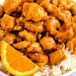 Close up picture of orange chicken with a slice of orange.