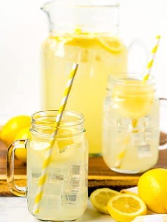 Lemonade that is homemade in mason jar cups and a large pitcher and lemons in the background.