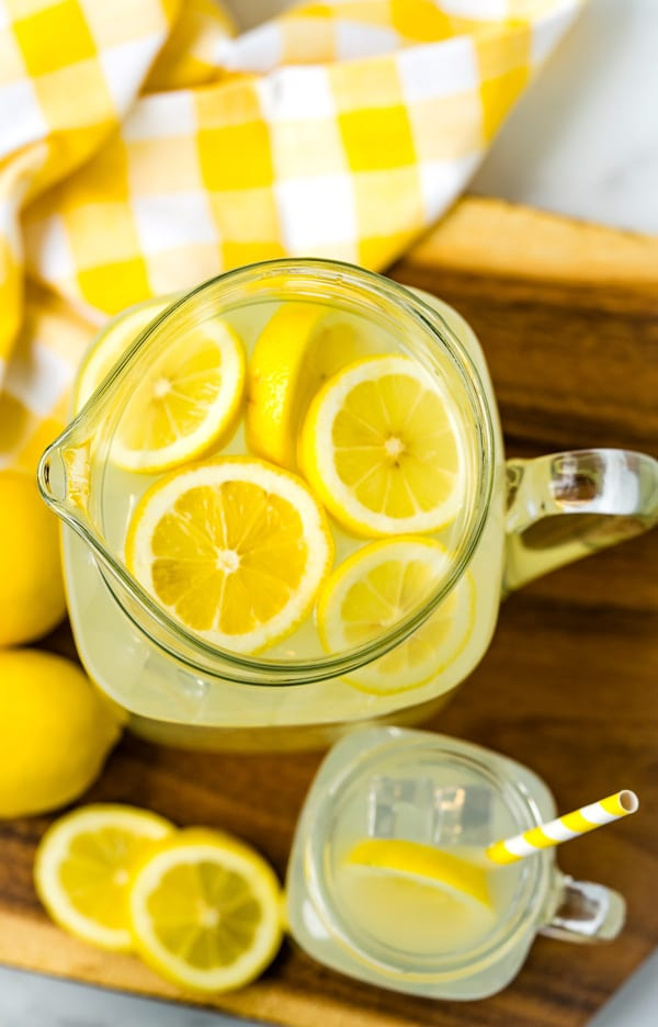 An overhead picture of lemonade in a pitcher with some in a glass that has a paper straw in it.