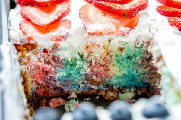 The inside of a 4th of July Poke Cake where you can see where Jell-o has been poured into the holes.