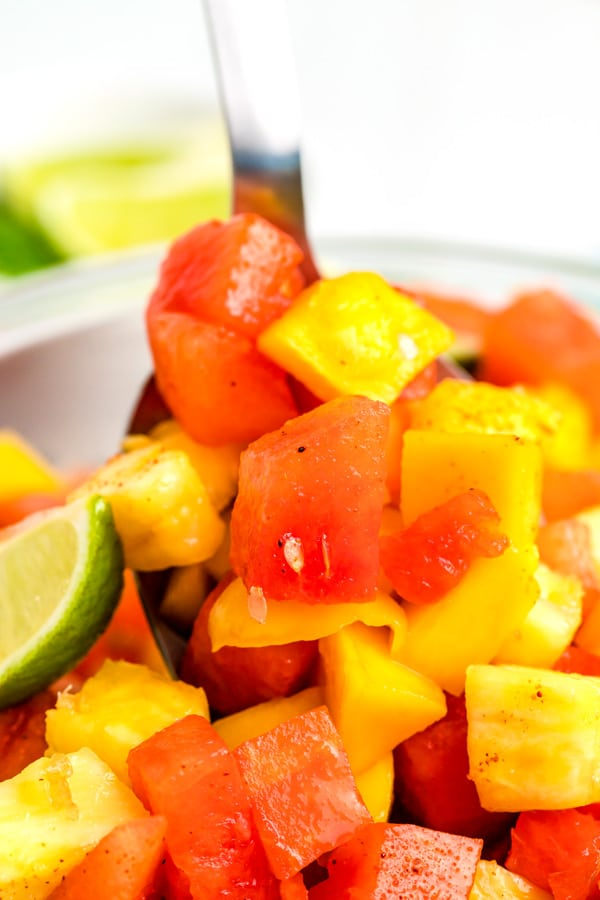 A close up picture of the Mexican fruit salad with a serving spoon getting a scoop of the fruit.