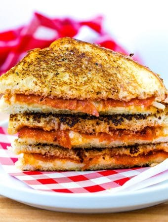 3 Pizza Grilled Cheese stacked on top of each other on a plate.