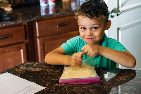 A little boy crushing up crackers in a Ziplock bag.