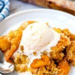 Warm peach cobbler on a white plate with a scoop of vanilla ice cream on top.