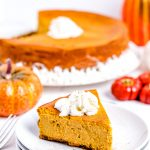 A slice of pumpkin cheesecake on a white plate and garnished with whipped cream.