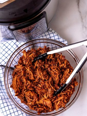 An overhead picture of a bowl full of shredded pork with an Instant Pot in the background.