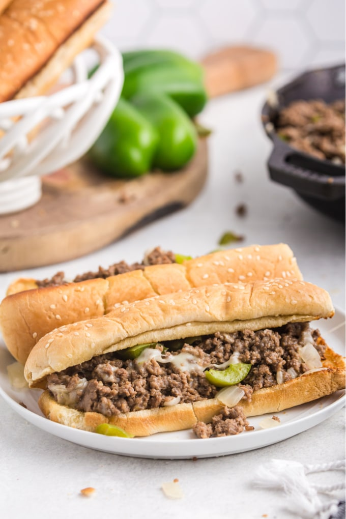 Two Philly Cheesesteak sloppy joes on a white plate with more of the filling in the background.