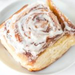 A close up picture of an overnight cinnamon roll on a white plate.