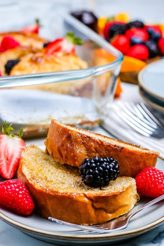 Two slices of overnight French toast bake on a plate with berries.