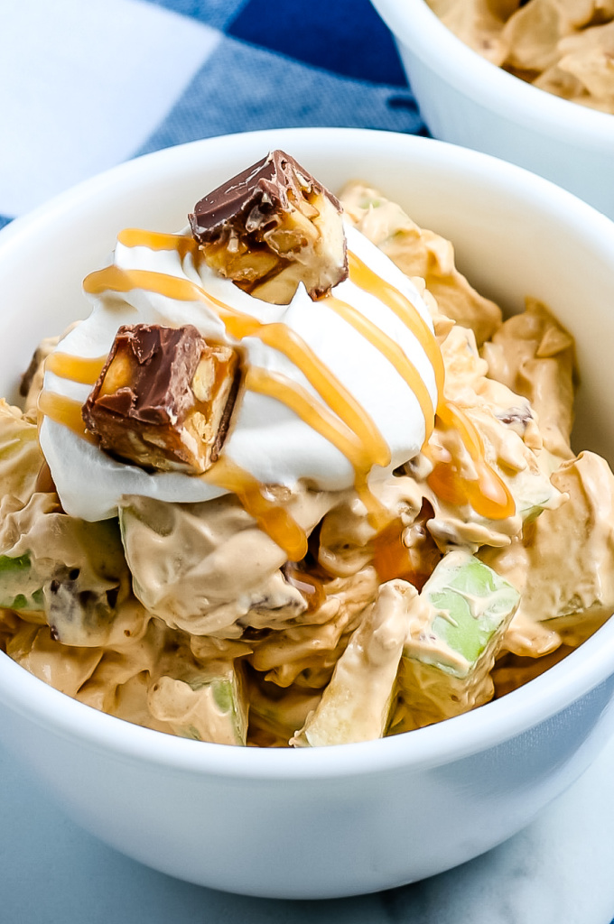 Snickers Salad is loaded with Granny Smith apples, butterscotch pudding, Cool Whip, caramel sauce, and of course, Snickers! Our family can't get enough of this irresistible dessert. via @easybudgetrecipes
