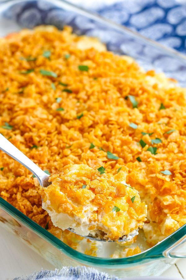 A spoon taking a scoop out of of the finished hash brown casserole.