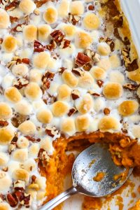 A spoon inside the sweet potato casserole with marshmallows and pecans.