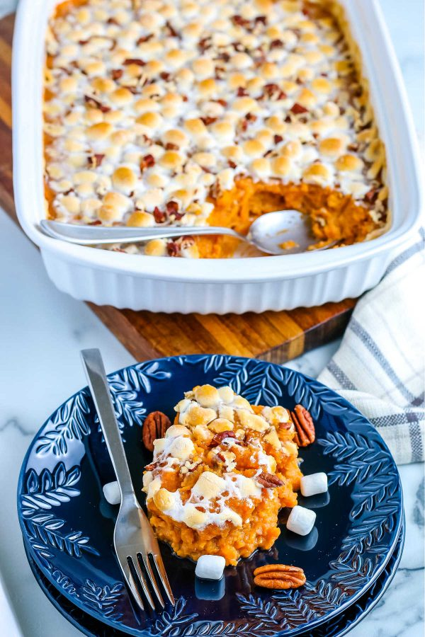 Some sweet potato casserole with marshmallows on a blue plate.