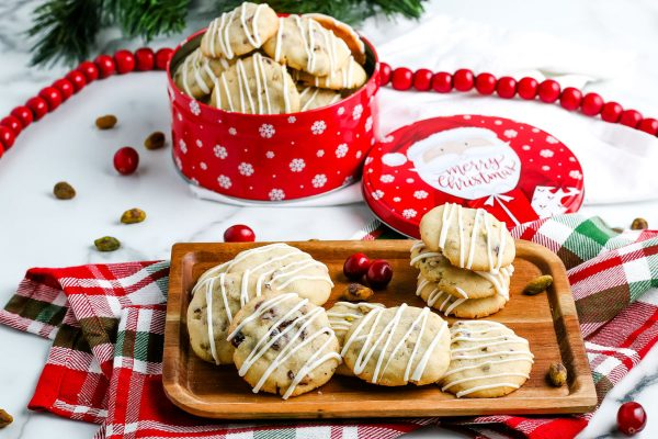 Pistachio cookies on a wooden tray with a tin of cookies for gifting in the background.