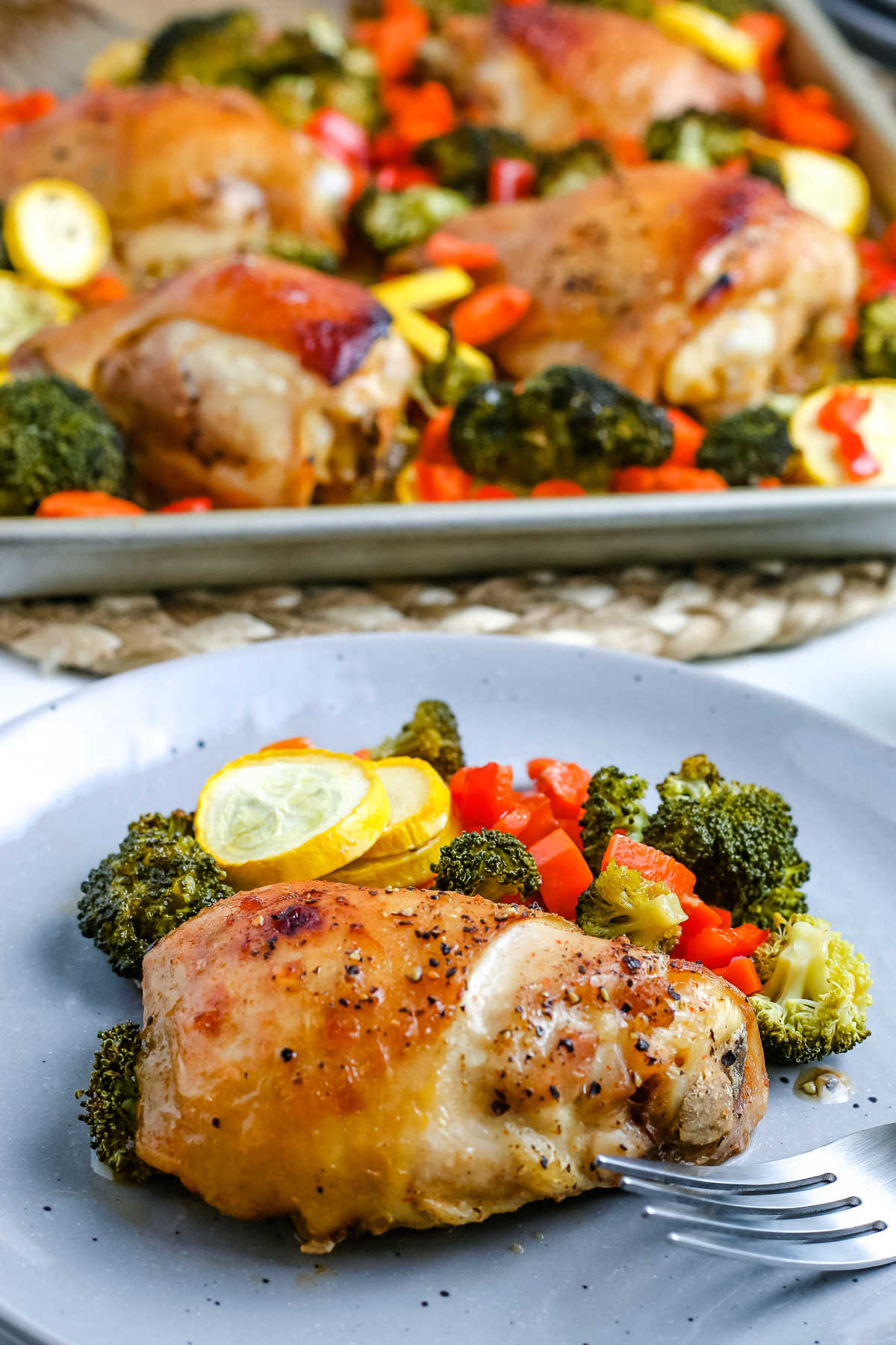 A chicken thigh and vegetables on a grey plate.