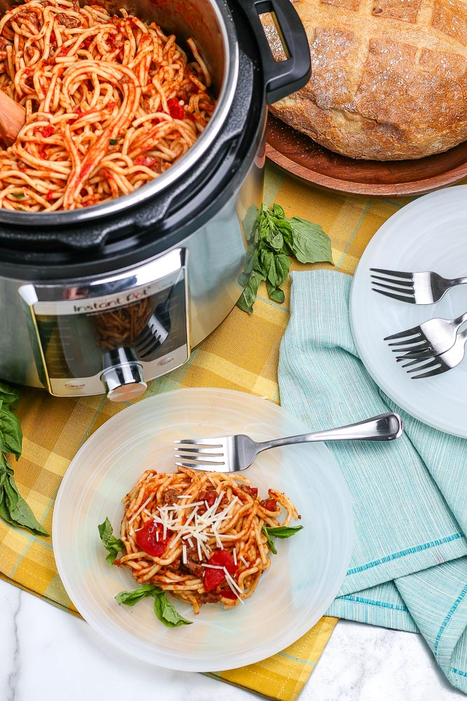 Instant Pot Spaghetti on a white plate plus more in the instant pot.