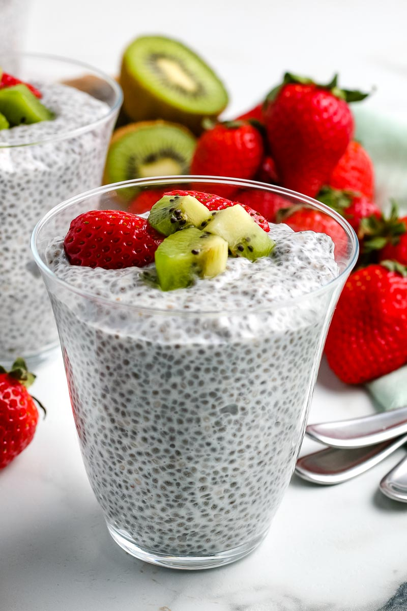 Chia Seed Pudding in a glass garnished with chopped strawberries and kiwi.