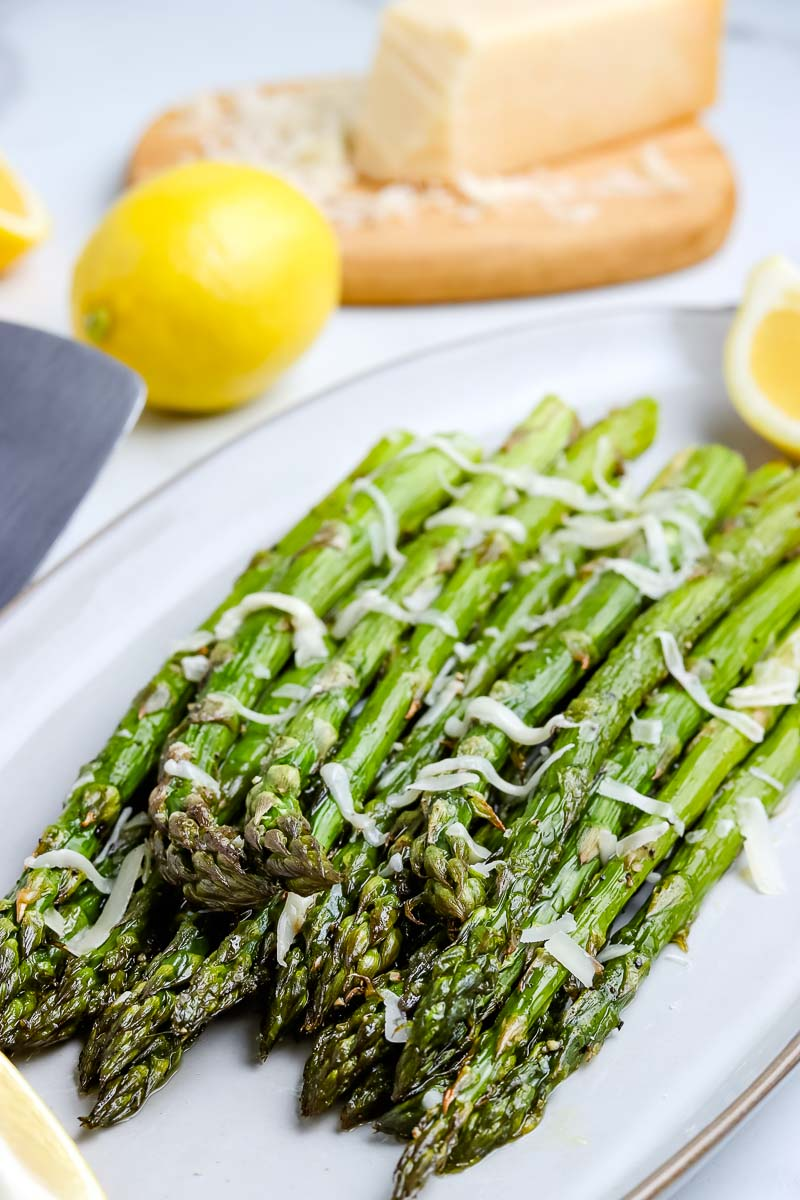 The finished roasted asparagus on a white serving plate.