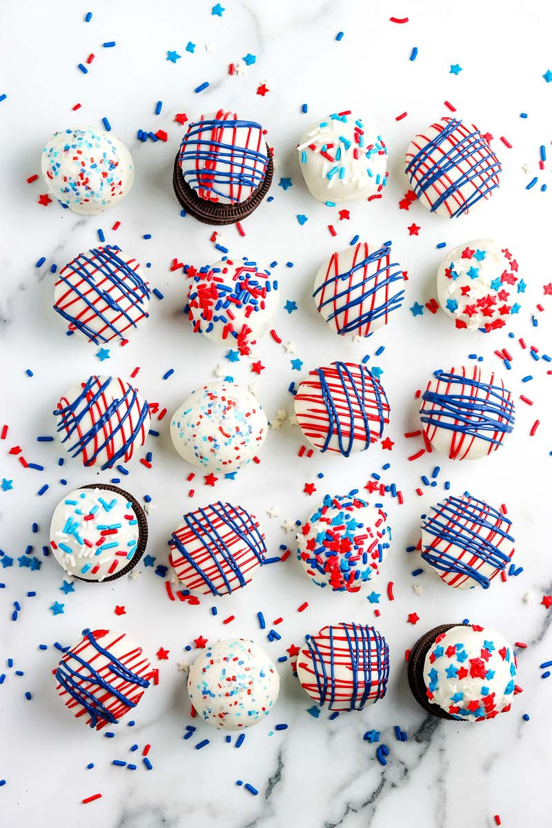 n overhead picture of rows of Patriotic Oreo Cream Cheese Truffles on a white platter.