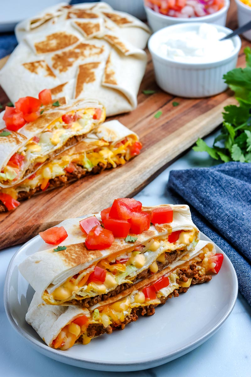A Copycat Taco Bell Crunchwrap Supreme cut in half and on a plate.